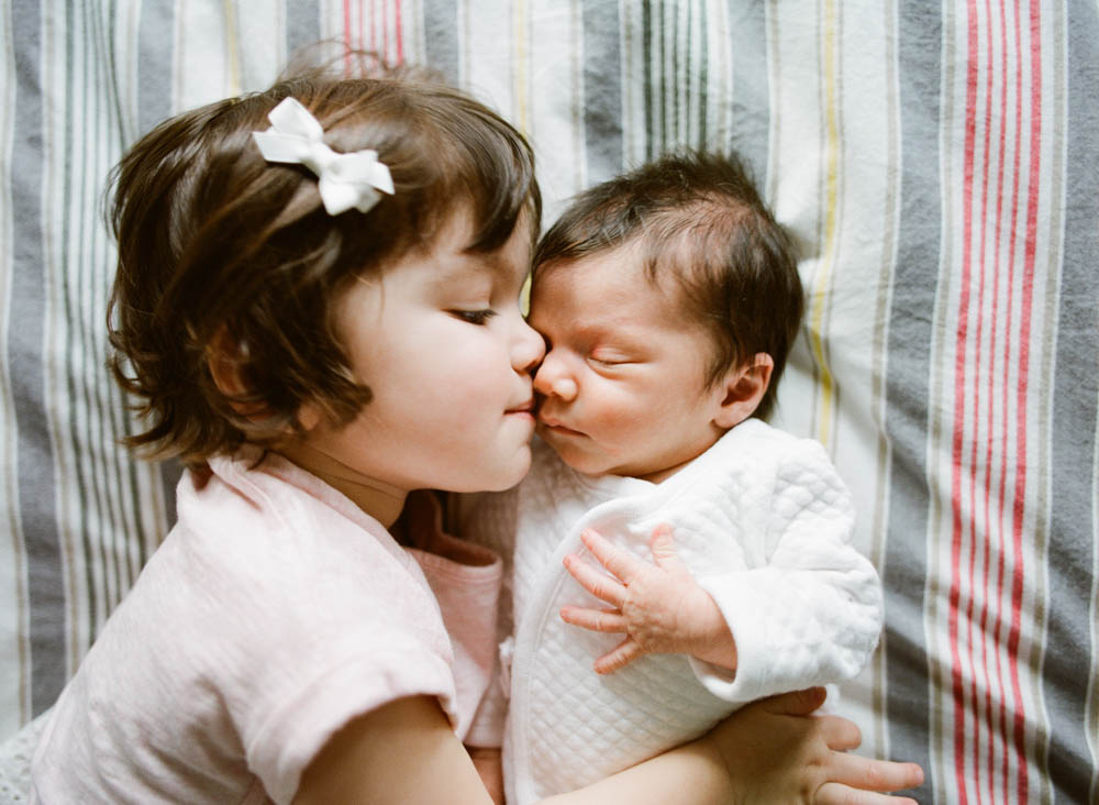 in home newborn session seattle wa : big sister kissing newborn baby girl
