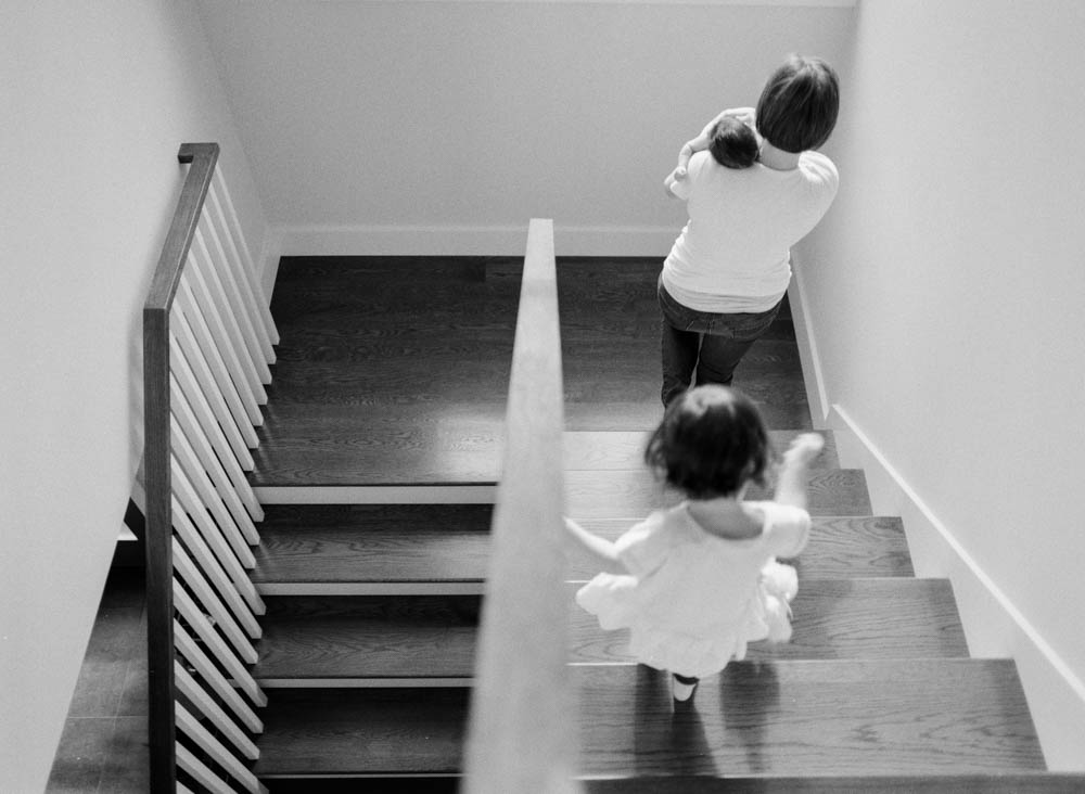 in home newborn session seattle wa : mom walking down stairs holding newborn and daughter following
