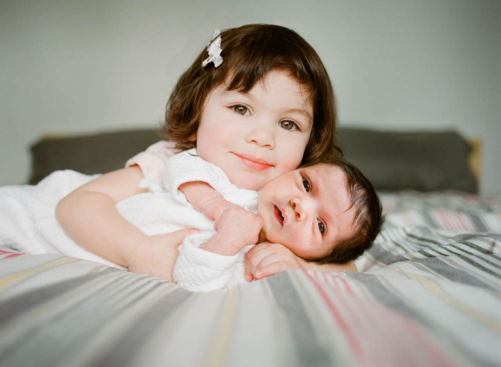 in home newborn session seattle wa : big sister cuddling newborn looking at camera while lying on bed