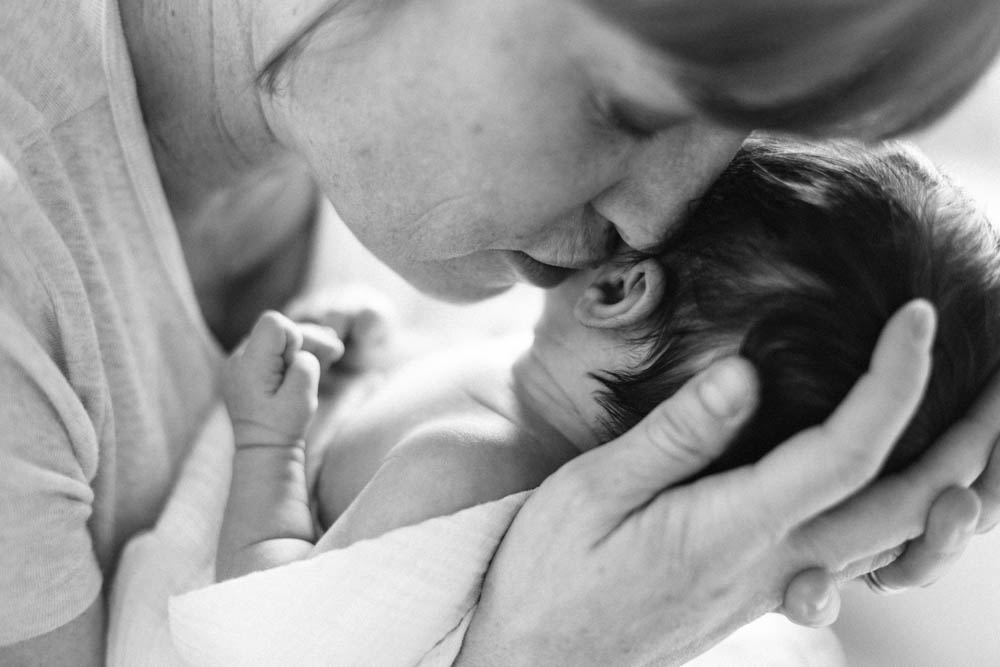 in home newborn session seattle wa : mom kissing newborn next to ear