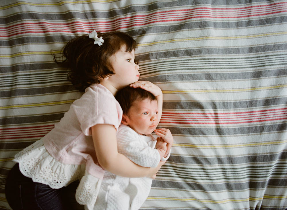 in home newborn session seattle wa : big sister and newborn sister cuddling sideways on bed