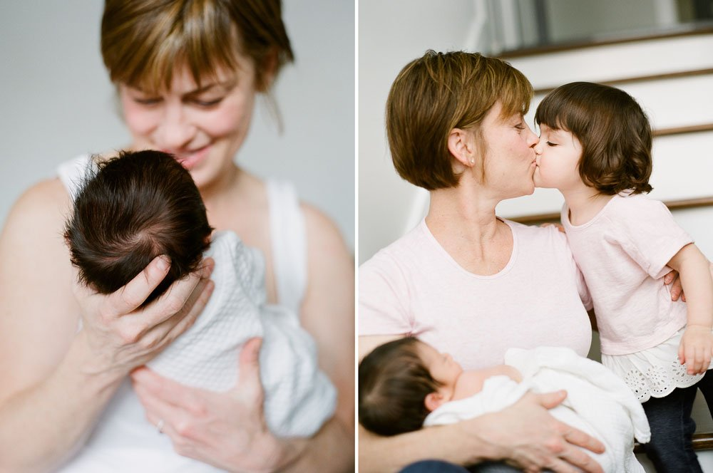 in home newborn session seattle wa : mom kissing older sister while holding newborn