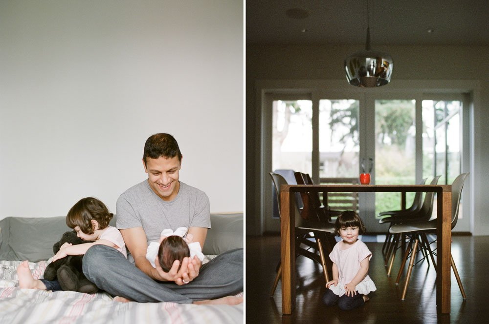 in home newborn session seattle wa : dad holding newborn and big sister sitting next to him cuddling bear