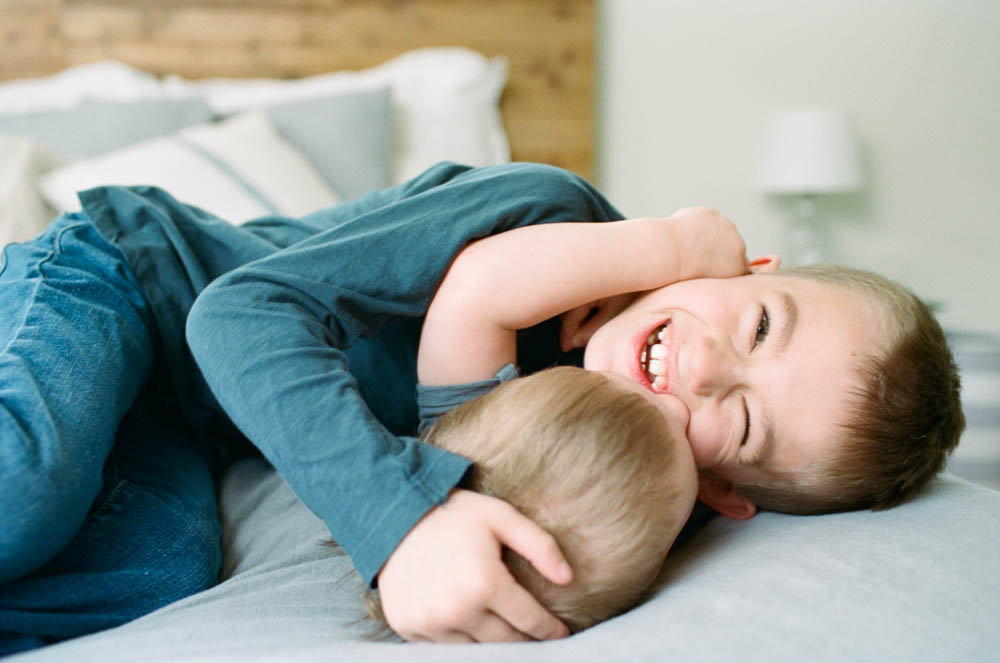 newborn film photographer seattle : brothers wrestling on bed