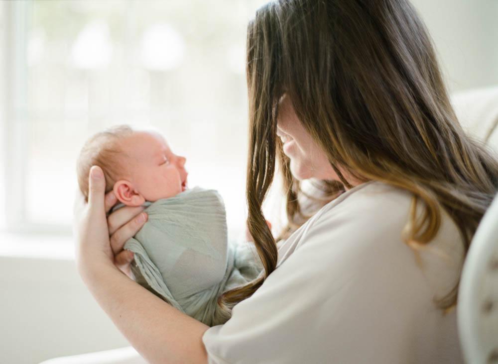 newborn film photographer seattle: mom holding newborn by window smiling