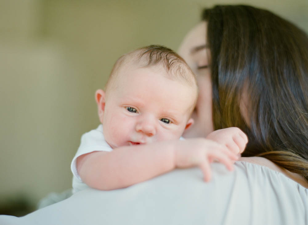 newborn film photographer seattle: mom kissing newborn over her shoulder