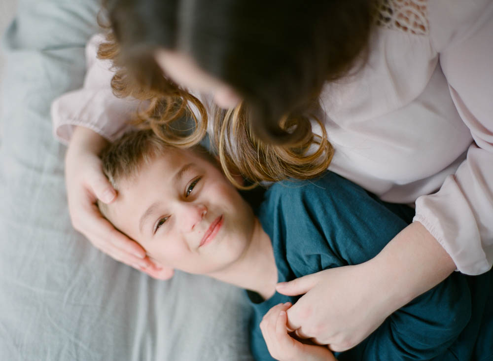 newborn film photographer seattle: mom cuddling with older son who is looking at camera
