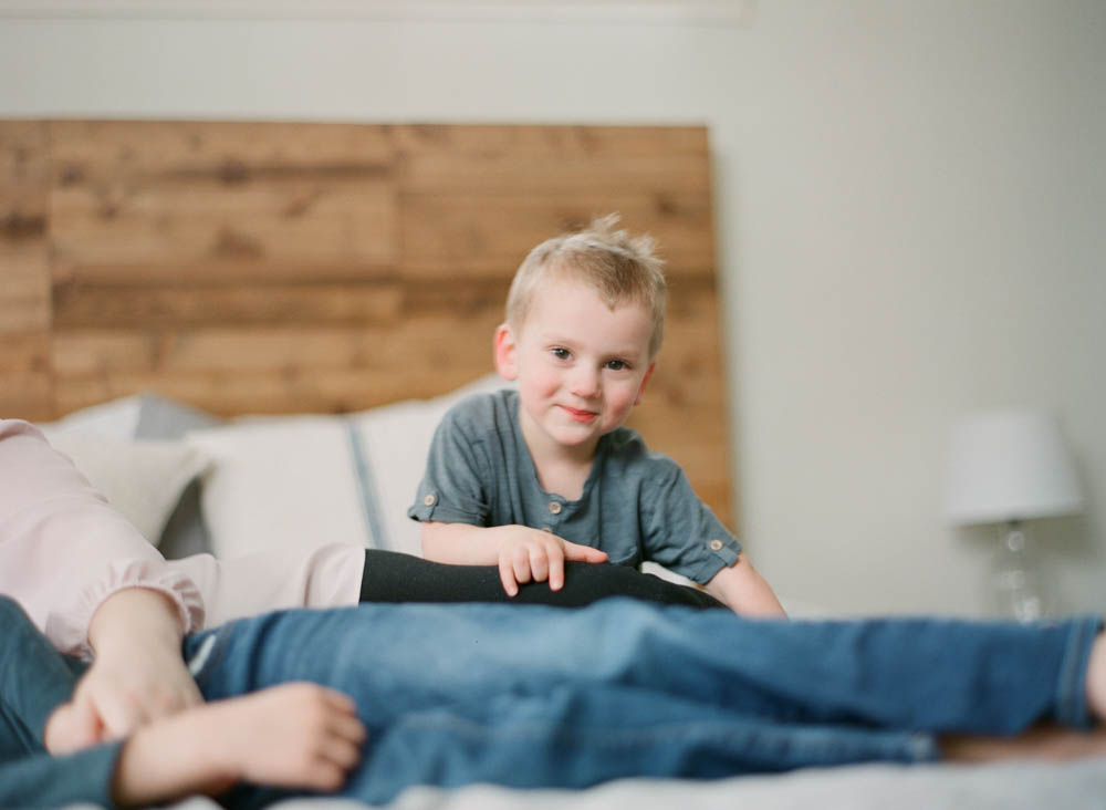 newborn film photographer seattle: young boy looking at camera smiling while sitting on bed