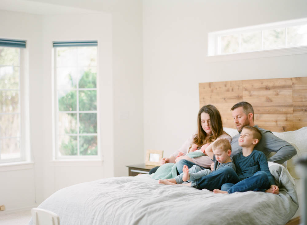 newborn film photographer seattle: zoomed out photo of family of five with newborn on bed
