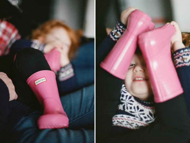 child photography Seattle : girl plays peek a boo through pink rain boots