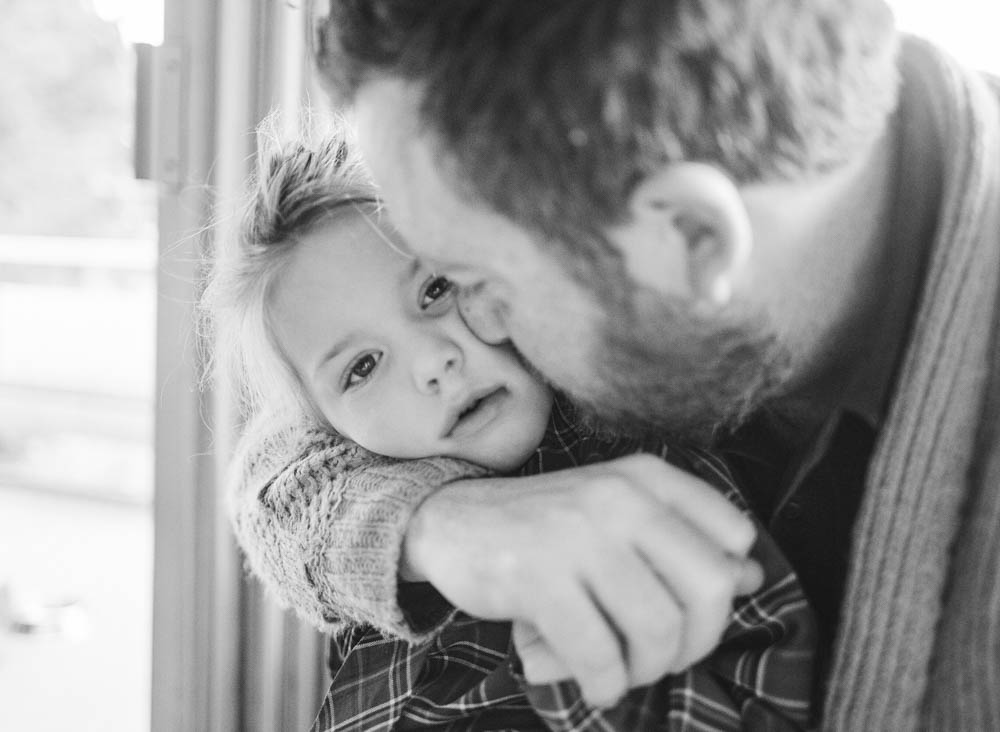 in home family photography seattle : dad kissing daughter