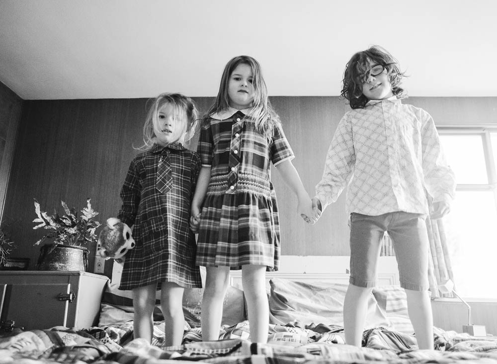 in home family photography seattle : three siblings standing on bed staring at camera