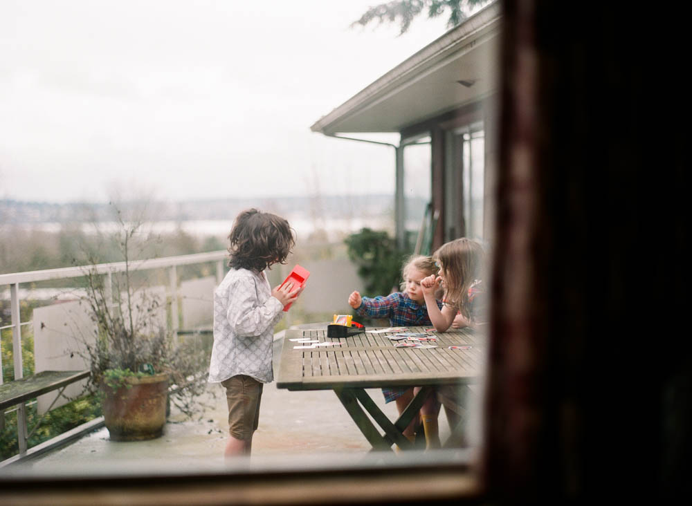 in home family photography seattle : kids playing uno on deck