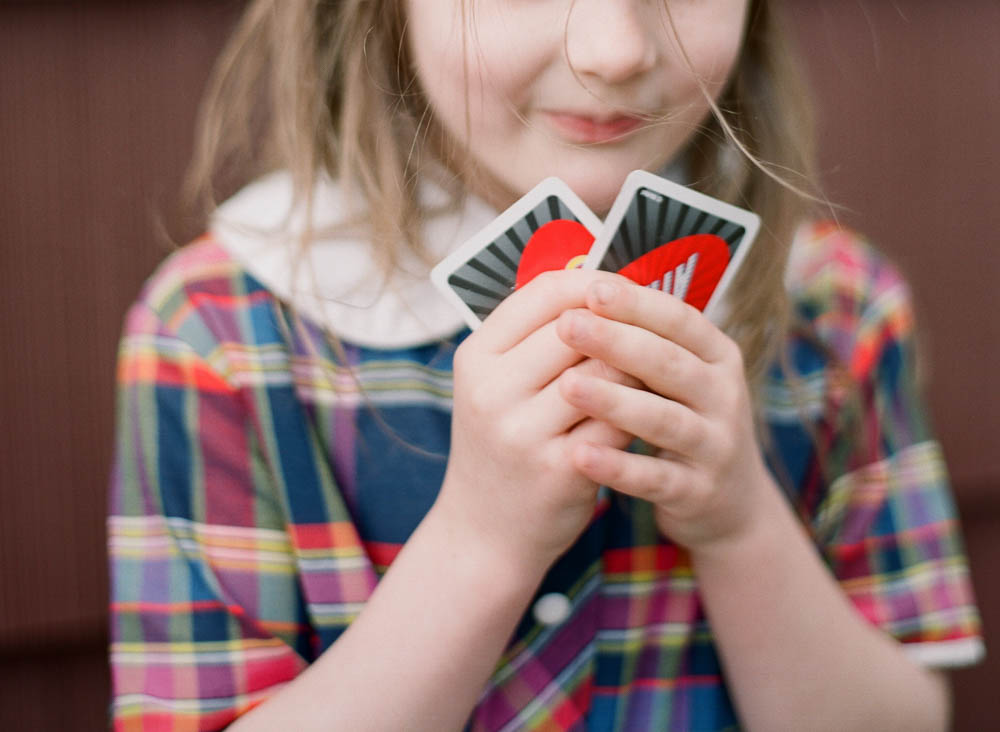 in home family photography seattle : close up of girl holding uno cards