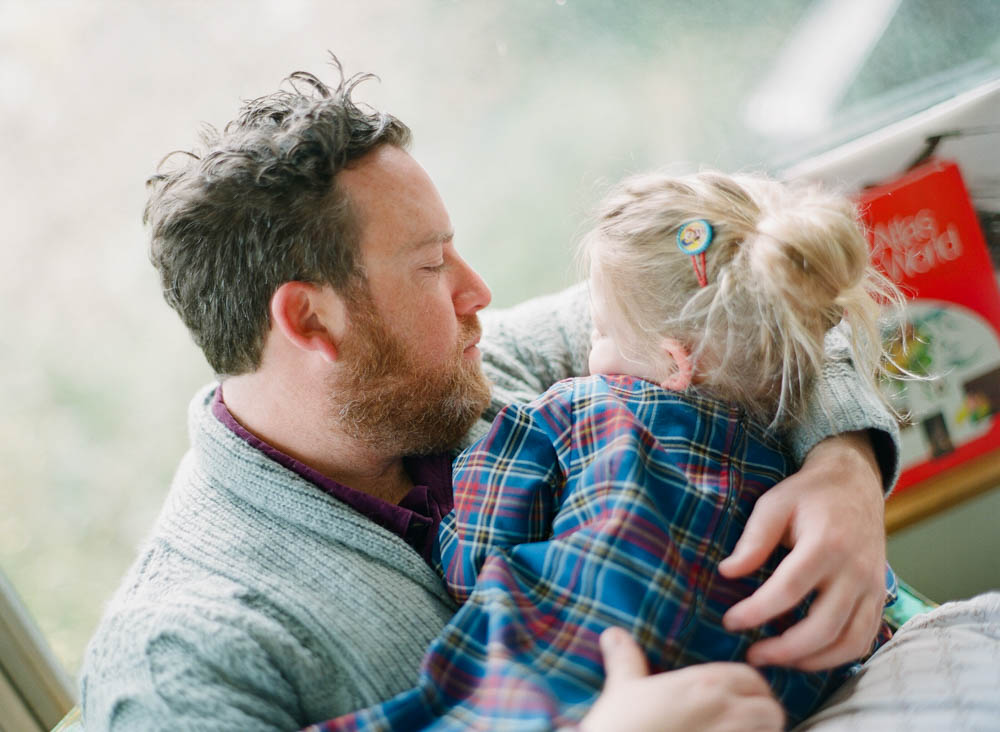 in home family photography seattle : dad cuddling daughter