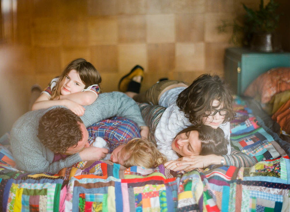 in home family photography seattle : family of five cuddling on bed