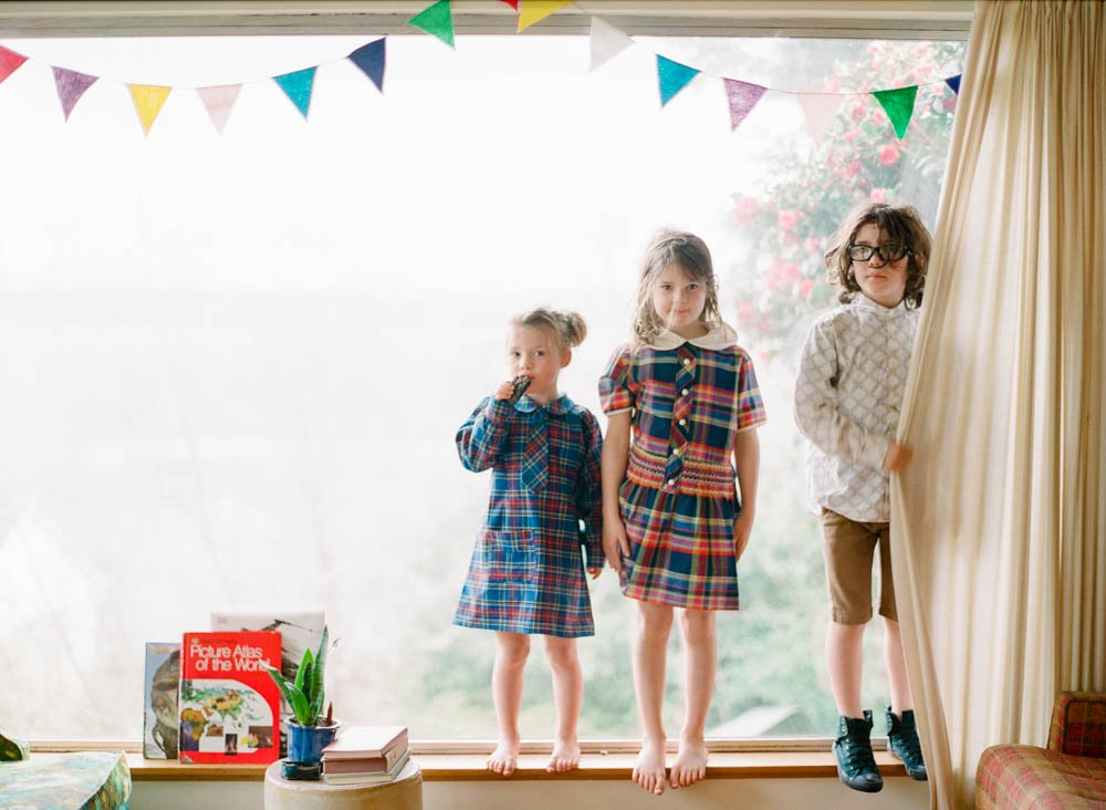 in home family photography seattle : kids standing on window sill