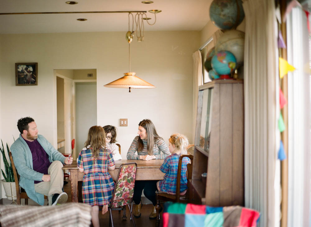 in home family photography seattle : family playing uno at table