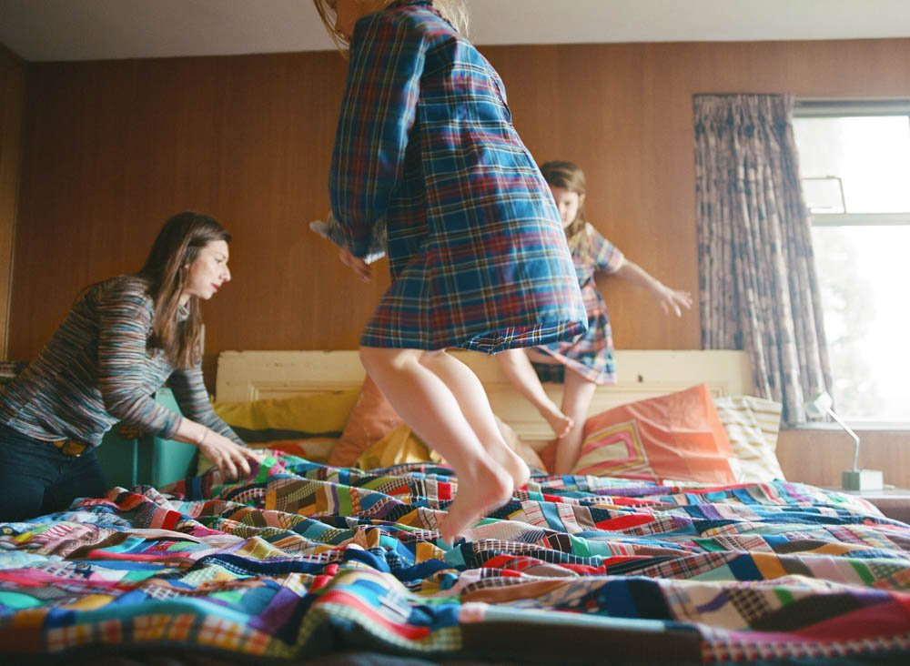 in home family photography seattle : kids jumping on bed