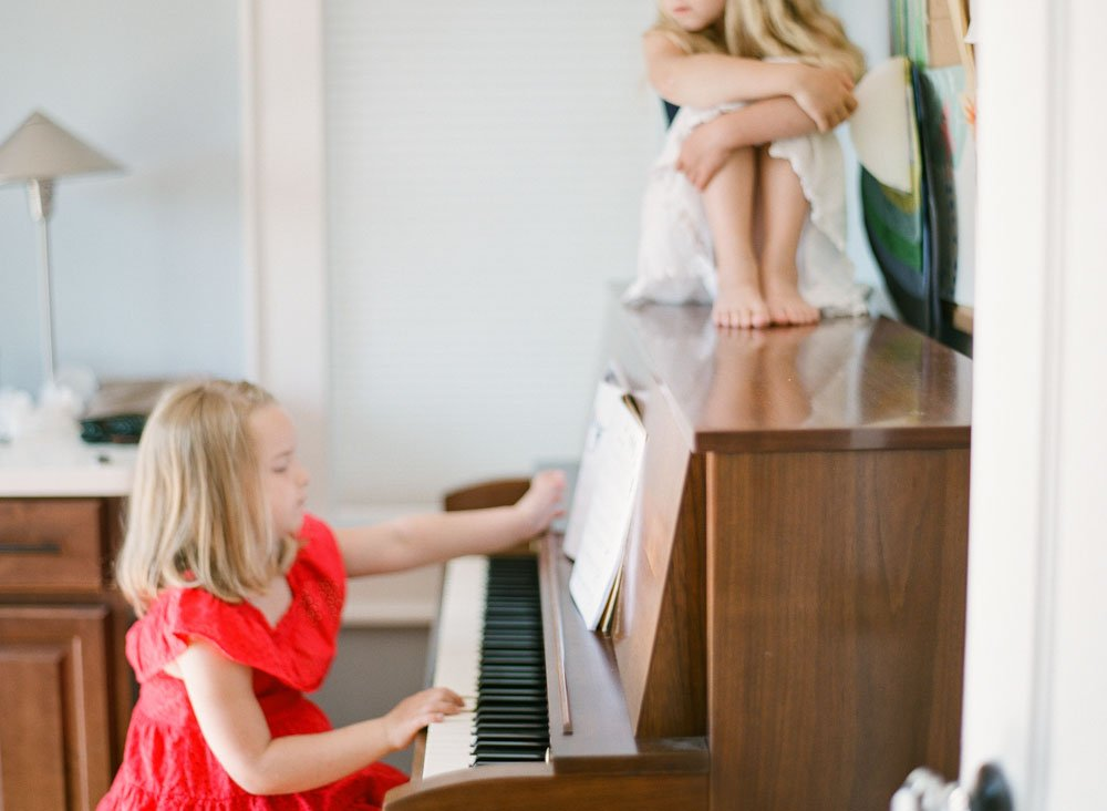 family photographers seattle : girl playing piano while sister listens