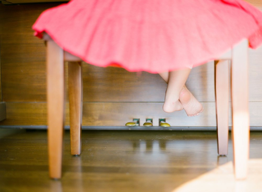 family photographers seattle : girl sitting on piano bench