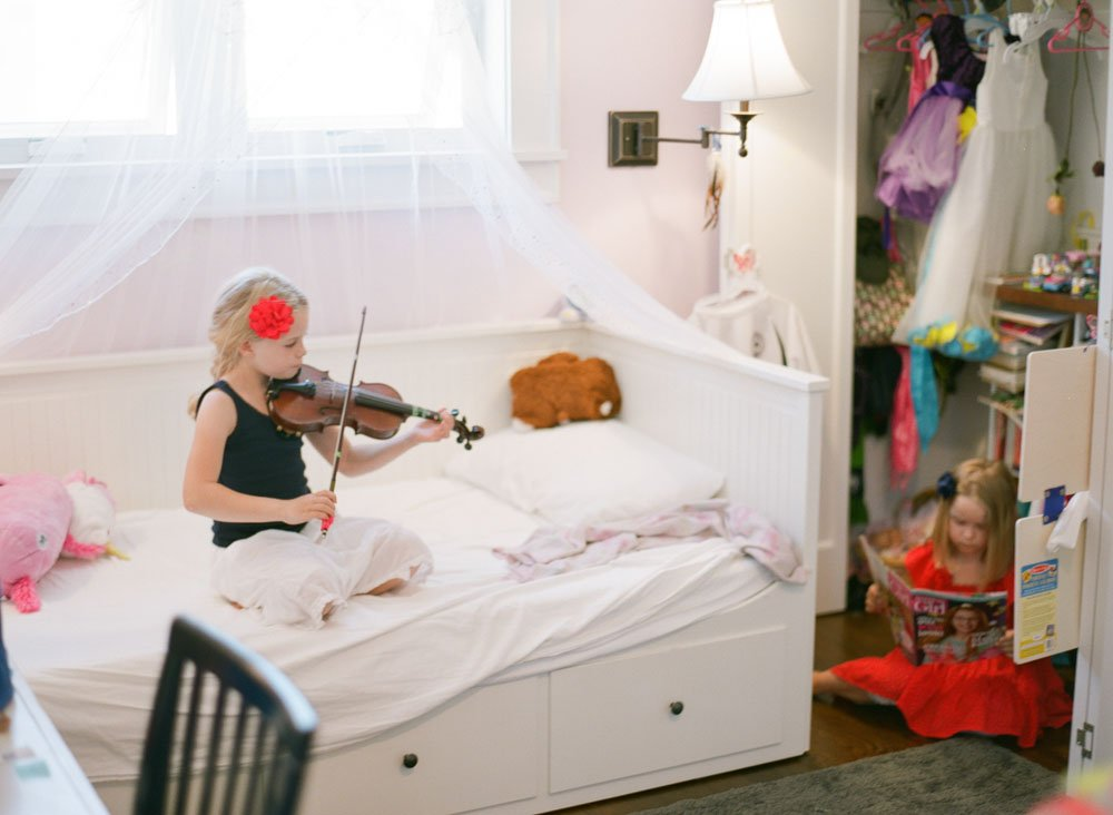 family photographers seattle : girl playing violin in bedroom