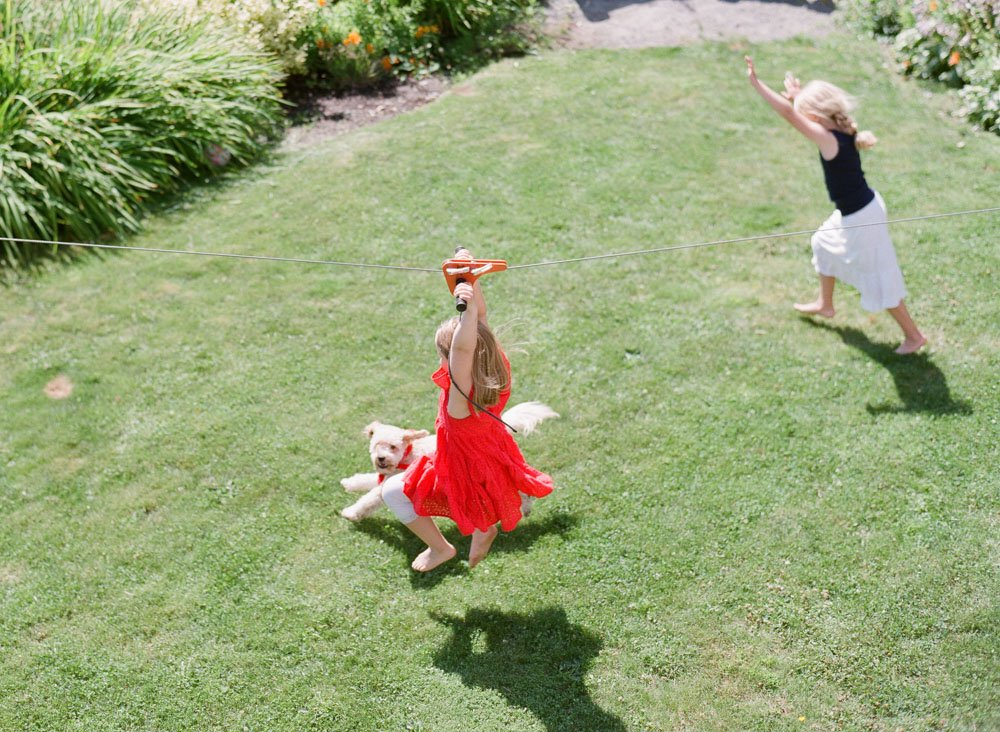 family photographers seattle : sisters doing zip line in backyard