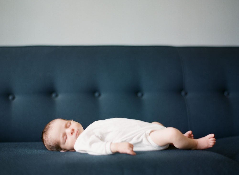 newborn photographers seattle : newborn baby sleeping on blue couch