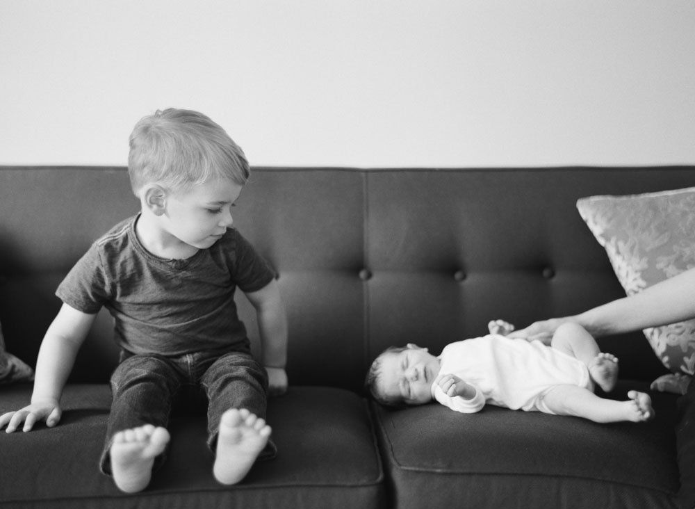 newborn photographers seattle : toddler sitting on couch looking over at baby brother