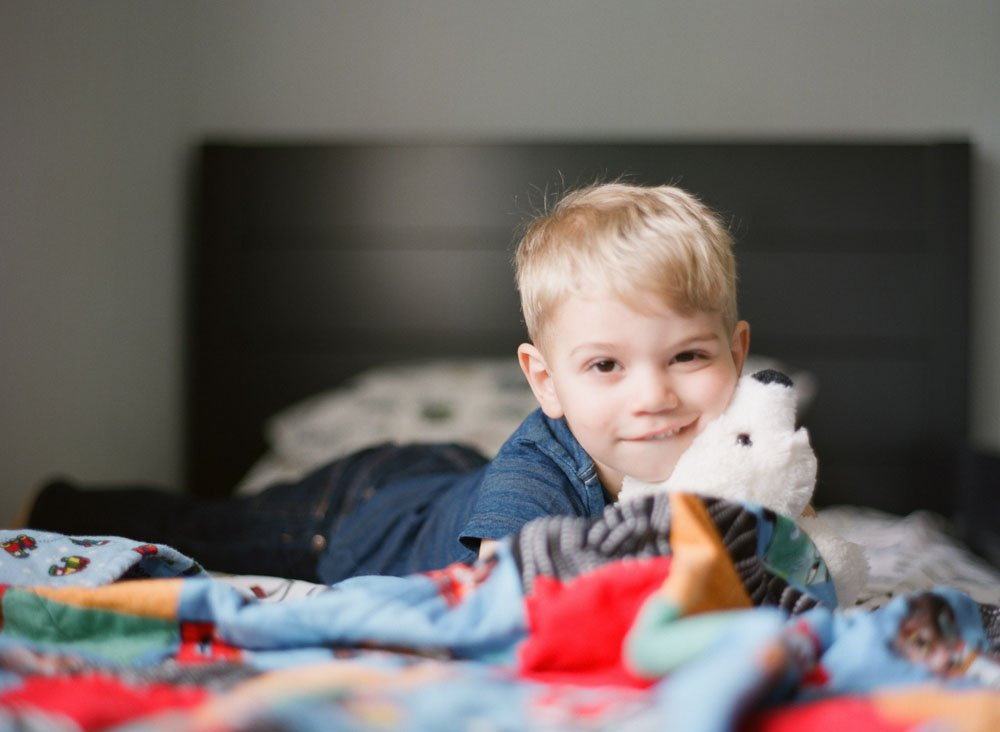 newborn photographers seattle : toddler snuggling stuffed animal laying on his bed