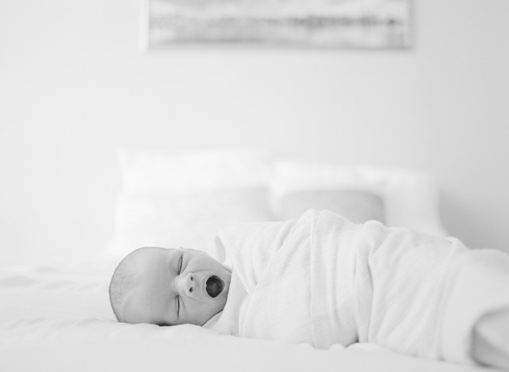 seattle infant photography: newborn yawning on bed