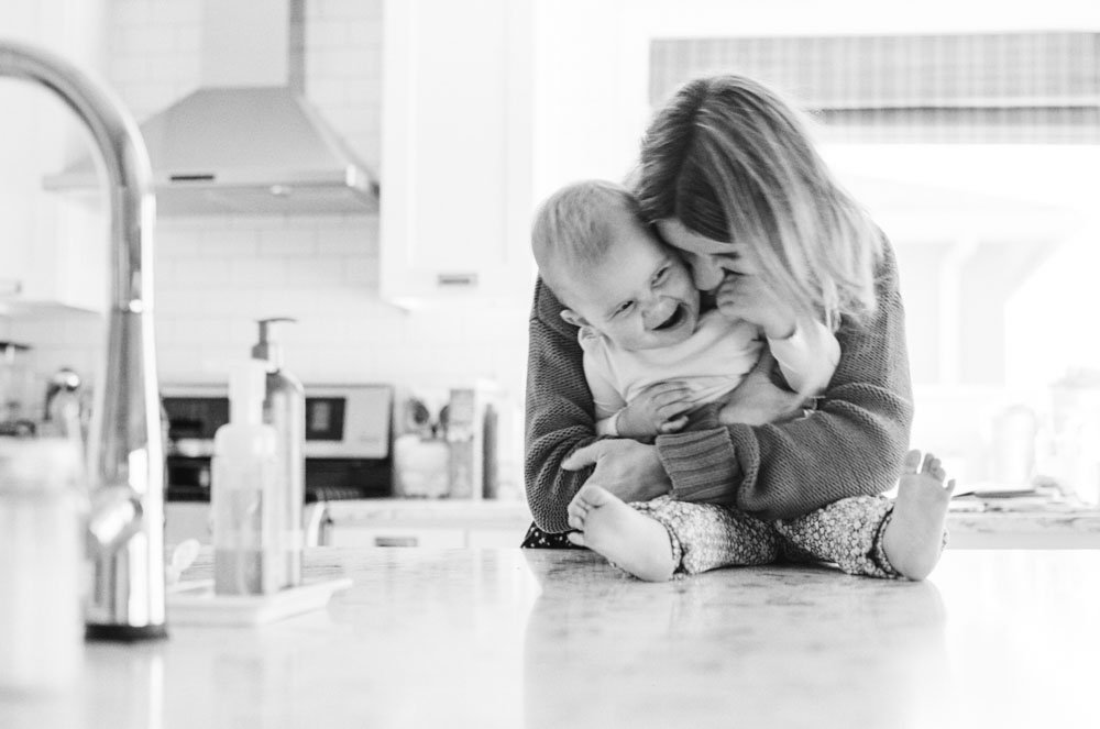 child photography seattle : mom cuddling baby on kitchen counter