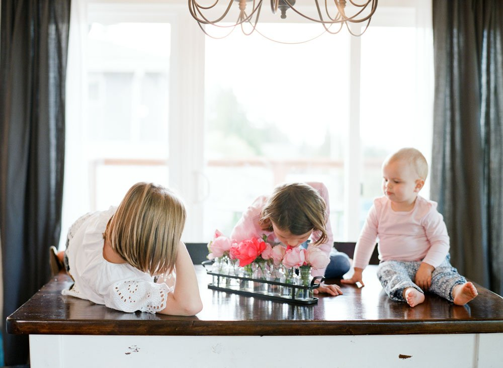 child photography seattle : sisters smelling roses on dining table