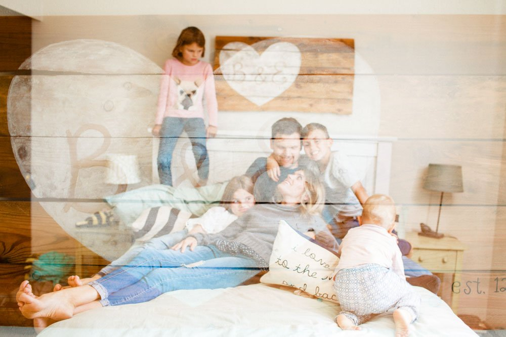 child photography seattle : double exposure of family on bed