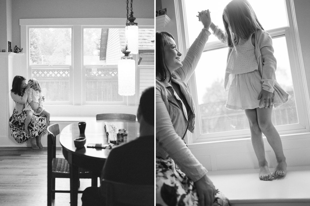 west seattle newborn and family photographer : mom and daughter holding hands by window
