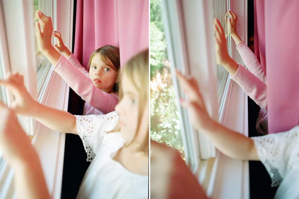why your house doesn't have to be clean for family photos : girls finger drawing on window behind curtain