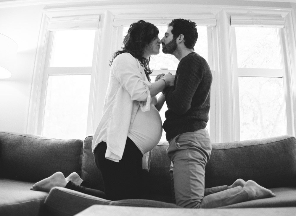 maternity photographer seattle : couple kissing kneeling on couch