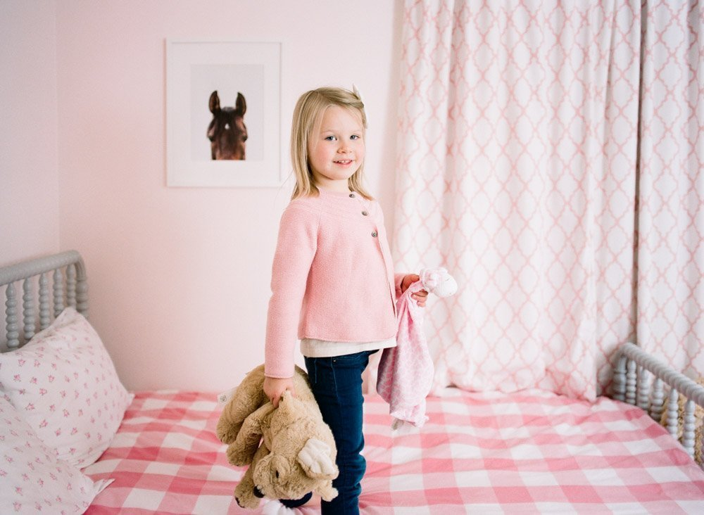 girl standing on pink bed in pink room looking at camera