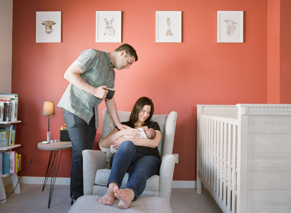 mom rocking baby in nursery while dad checks in on them