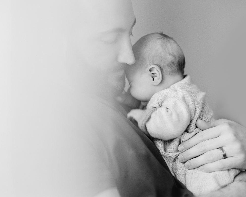 Dad snuggling newborn baby