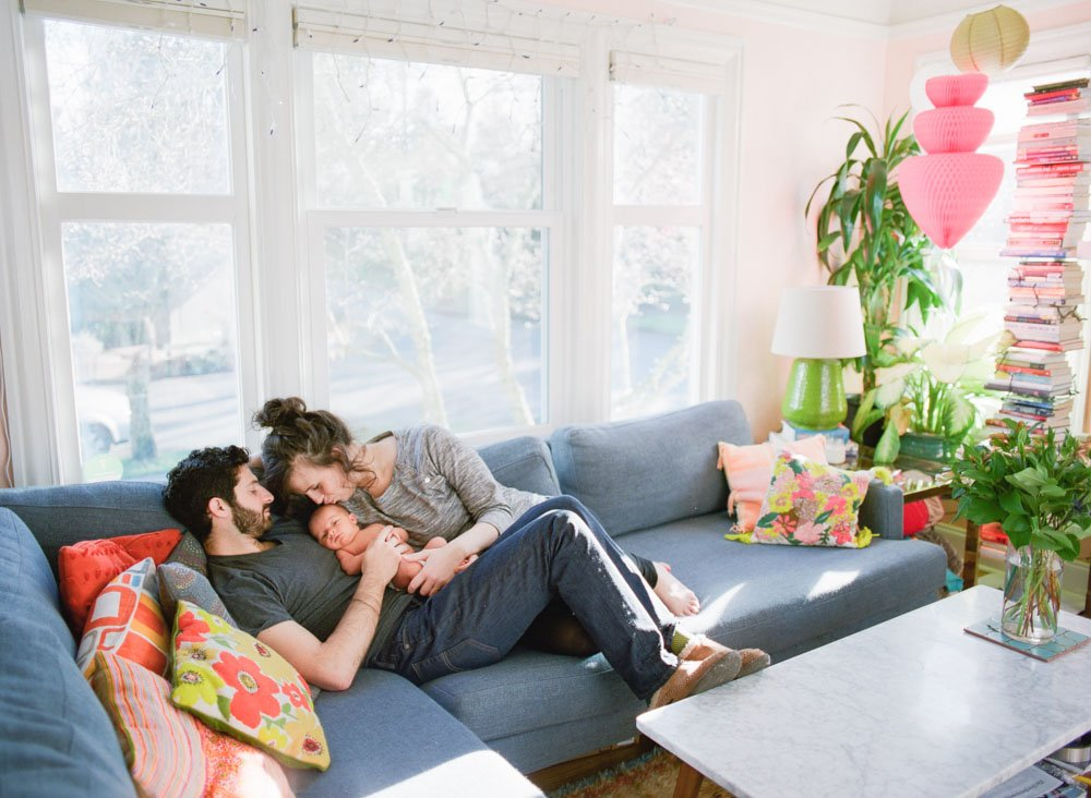 mom and dad cuddling newborn on living room couch