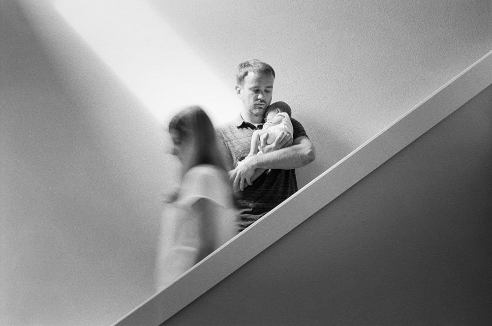 dad holding newborn on stairs while mom walks by