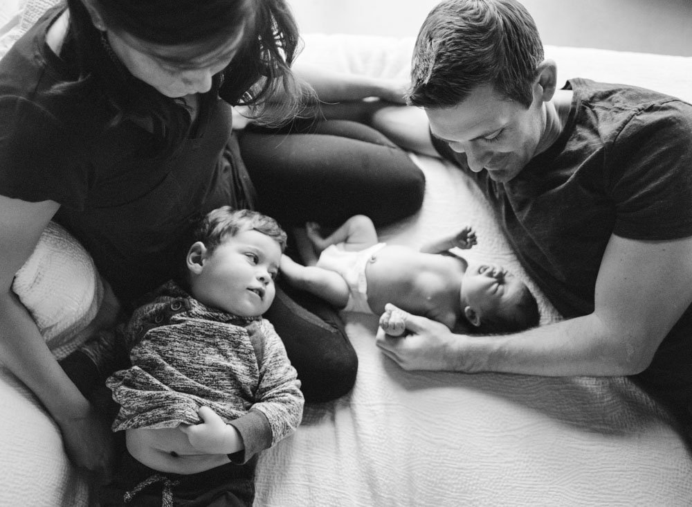 family with toddler and newborn hanging out on bed