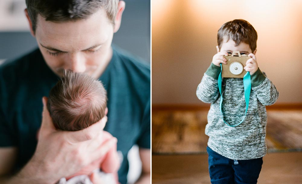 dad kissing newborn and child taking pretend photo