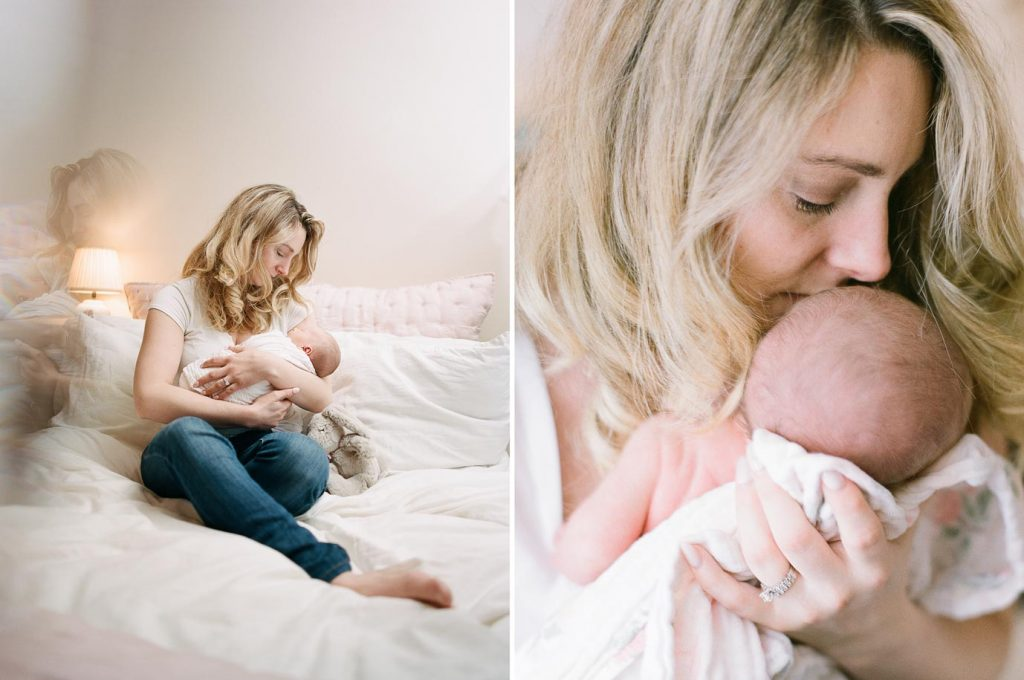 mom kissing newborn baby while sitting on bed